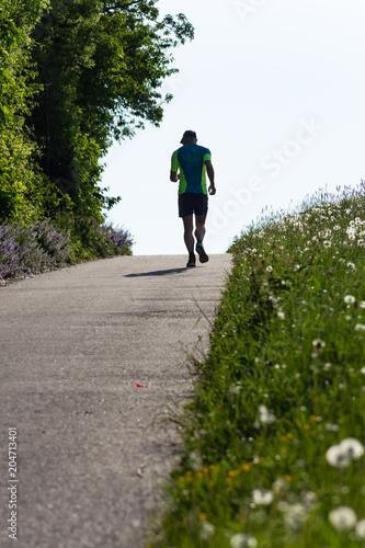 man running uphill springtime morning Wallpaper Mural