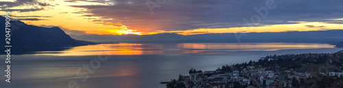 Photo Scenic view of sunset over the Leman lake with yellow sky with clouds and Alps mountains in background, Montreux, Switzerland