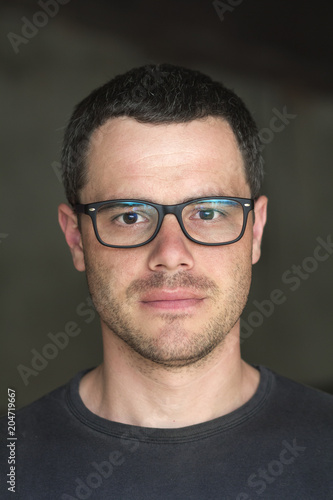 5a1d341ac2d0 Portrait of young handsome black-haired unshaven confident successful  intellectual man in glasses with white teeth and shiny black eyes on dark  background.