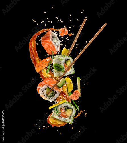 Poster Sushi bar Flying sushi pieces on black background