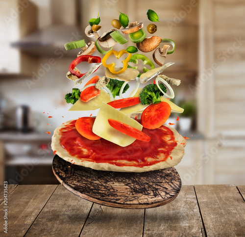 Flying pizza ingredients, served on wooden table