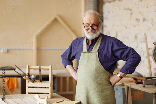 Fotomural  cheerful senior citizen is ready to work in the workshop