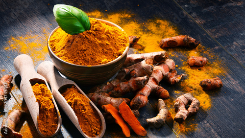 Foto op Canvas Aromatische Composition with bowl of turmeric powder on wooden table