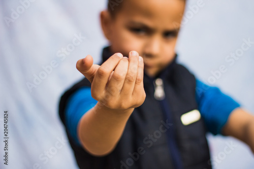 Serious little boy doing come here gesture Wallpaper Mural