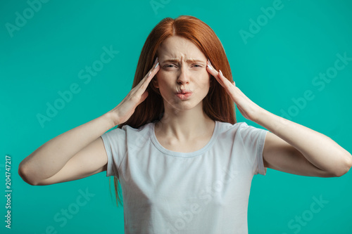 Fotografering  Portrait of stressed, frustrated or irritated woman with ginger hair isolated over blue background