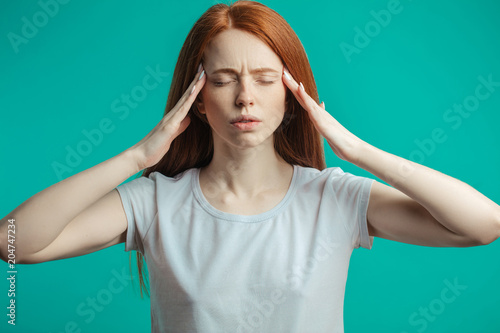 Fotografering  Closeup portrait of stressed shoked or irritated readhead young woman with closed eyes holding hands near her head as if she has a head ache isolated over blue background