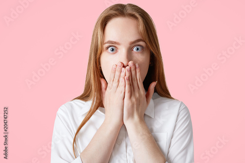 Photo Surprised beautiful young female with blue eyes popped out, covers mouth with fear, feels embarrassed, wears casual white shirt, isolated over pink studio background
