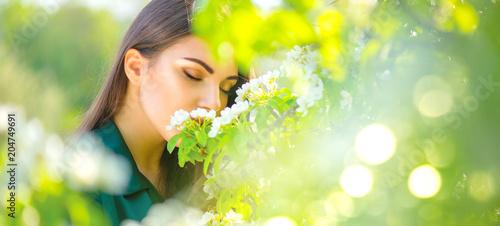 Fotografia  Beauty young woman enjoying nature in spring apple orchard, Happy beautiful girl