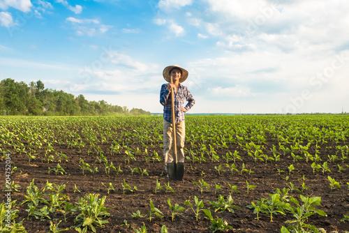 Fotografía Happy small farmer with spade in spring field