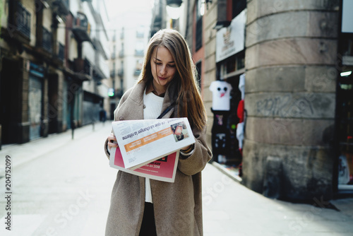 obraz dibond Young caucasian female stunned with the latest news she read in a morning newspaper amidst the street . Business woman in trendy clothes reading market news while going to the office.