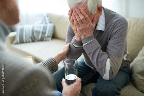 Valokuvatapetti Crop compassionate person consoling elderly man in assisted living home holding glass of water