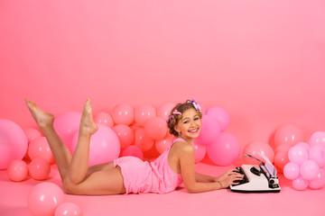 Obraz na płótnie Canvas Child in underwear with typewriter on pink background.