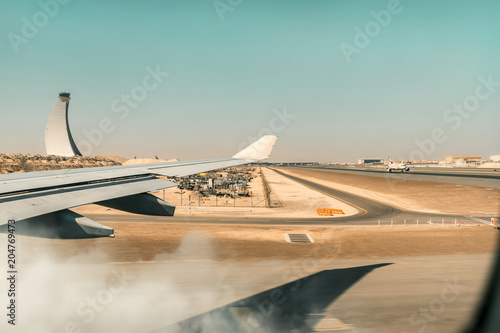 Poster Abou Dabi plane land - fast commercial airplane with passengers landing and ton the airport runway with speed and dust
