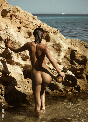 Foto op Aluminium Akt beautiful female model on the beach with naked body at sea and nature sunset.