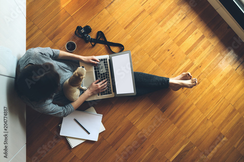 Top view photo of a woman using credit card for online payment via portable computer while sitting on a floor with a dog. Young hipster girl booking flight tickets online via laptop.