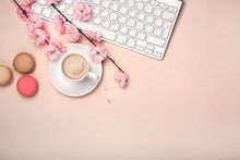 White Cup With Cappuccino, Sakura Flowers, Keyboard, Macarons On A Pastel Pink Background.