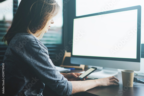 young girl entrepreneur is developing the concept of a new business project sitting in a cozy office. blank screen for text or design. Attractive female student typing text message on a smartphone