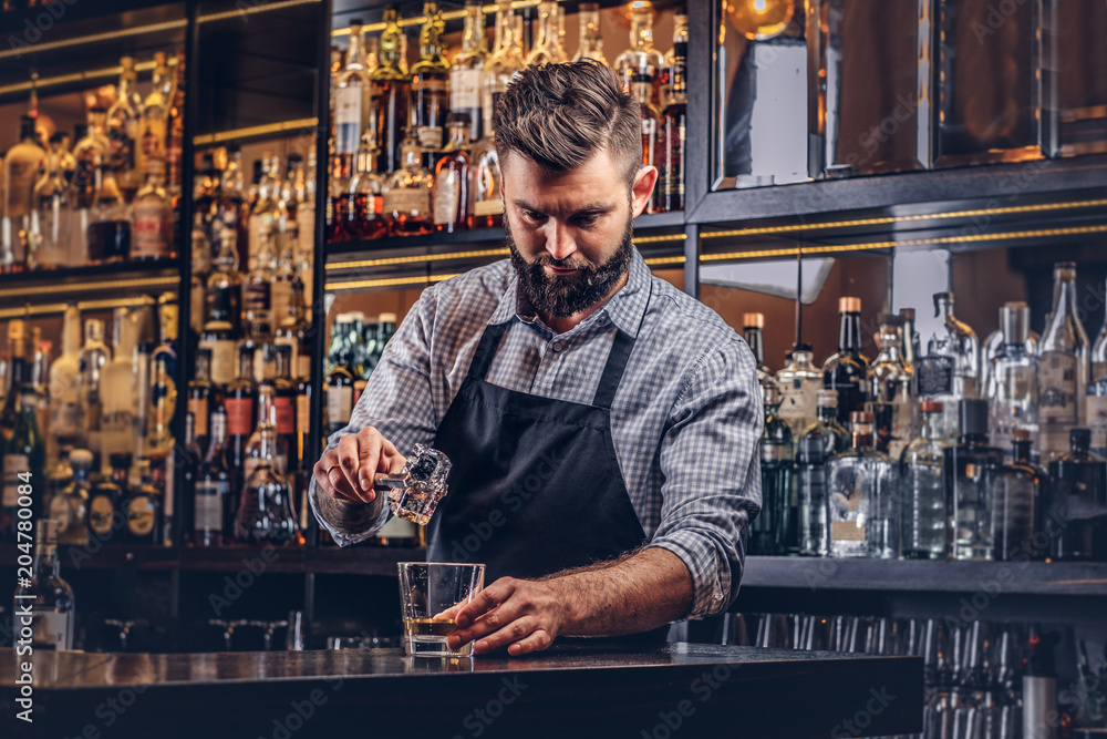 Fototapeta Stylish brutal barman in a shirt and apron makes a cocktail at bar counter background.