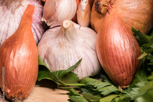 Foto op Canvas Aromatische garlic onion shallot parsley on a wooden board