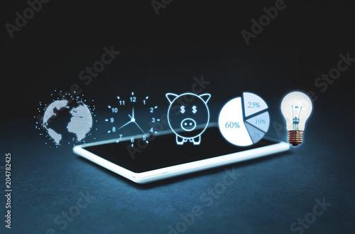 Fotografía  Globe, clock, piggy bank, pie graph and light bulb on digital tablet