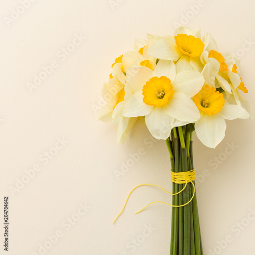 Poster Narcis White daffodil bouquet on yellow pastel background with copy space.