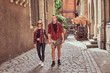 Young hipster couple, handsome skater and his girlfriend walking around an old narrow streets of Europe.