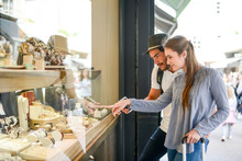 Cheerful Young Couple Looking At Jewelry Shop Window In Summer