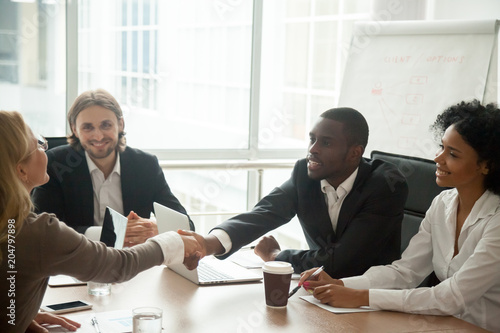 Fotografía  African businessman and caucasian businesswoman shaking hands over conference ta