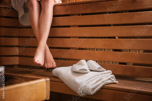 Fotografía Young woman sitting on wooden bench in sauna