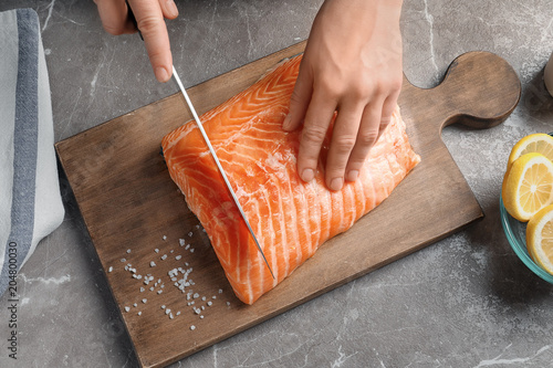 Fotografie, Obraz  Woman cutting raw salmon fillet on wooden board, top view