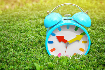 Alarm clock on green plants, outdoors. Time change concept