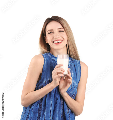 Beautiful young woman drinking milk on white background