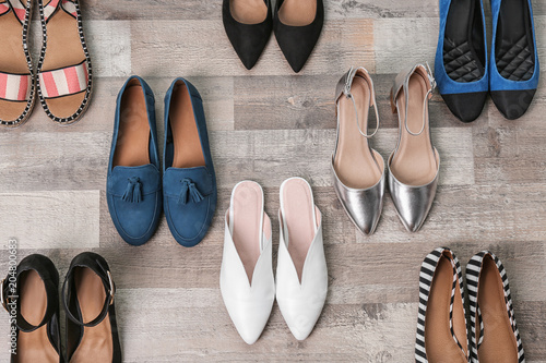 Different female shoes on wooden background, top view