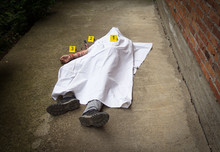A Dead Man Covered With White Sheets. A Bloody Knife In The Background