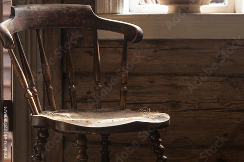 Vintage wooden chair, old cottage next to window