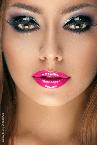 Fotografía  beauty face of young woman with glittering eyeshadows and pink gloss lips makeup