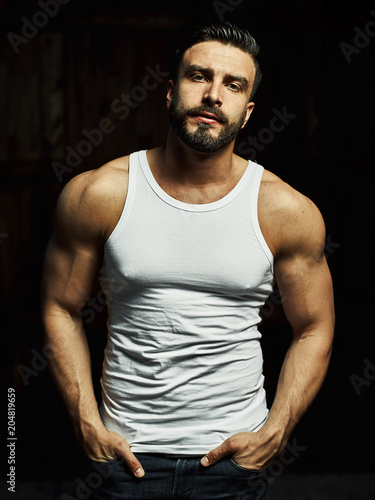 Fotografie, Obraz  A strong, a serious, muscular man in a white t-shirt is worth and looks in camera