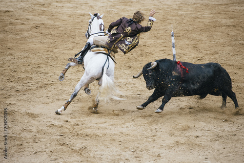 Tuinposter Stierenvechten Corrida. Matador and horse Fighting in a typical Spanish Bullfight