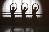 graceful silhouettes of ballerinas in the background of a window in ballet class