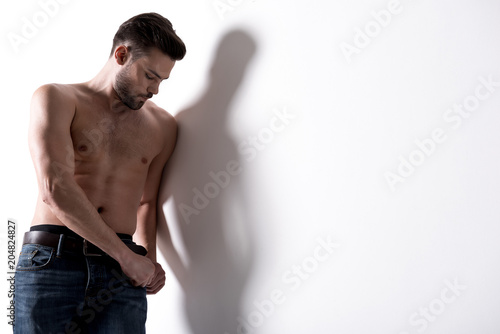 Foto op Aluminium Akt Male beauty concept. Young attractive sexual muscular man is posing with naked torso. He is leaning on wall while. Copy space in the right side