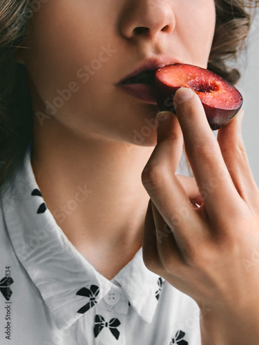 Fresh ripe plum Girl is eating a half of plum Close-up photo template with copy space