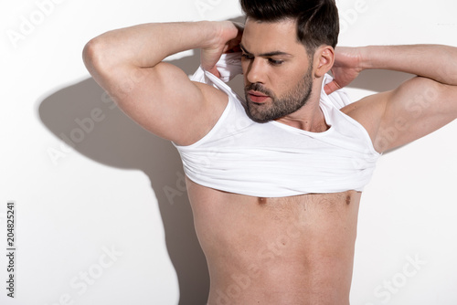 Foto op Plexiglas Akt Young sexual man is taking off his shirt while standing against light background. He is looking aside thoughtfully while holding hands behind his head
