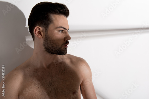 Foto op Plexiglas Akt Heavy thoughts. Profile of young muscular topless man is standing against light background and expressing confidence. Copy space in the right side. Geometric shadows on the wall