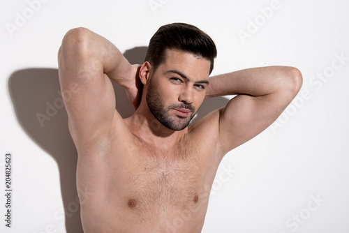 Foto op Plexiglas Akt Perfect skin. Portrait of charming topless guy is standing against light background and demonstrating his smooth armpits. He is raising his arms up while looking at camera confidently