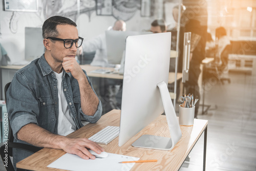 Photo  Portrait of pensive man looking at digital device while locating at desk