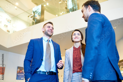 Fototapety, obrazy: Low angle view at group of cheerful young business people smiling happily while chatting in modern office building