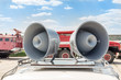 canvas print picture - Pair of big retro loudspeakers on car roof. Fire trucks on background. Urgent or emergency announcement concept