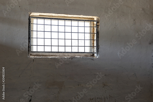 Cuadros en Lienzo Old white wall with window covered by iron grate