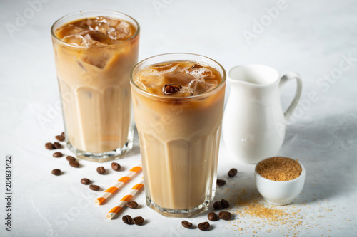 Fotografia  Ice coffee in a tall glass with cream poured over and coffee beans