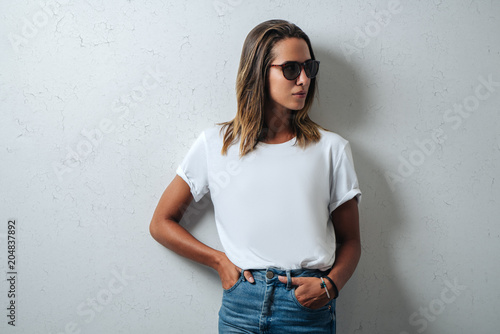 Obraz Stylish woman in white blank t-shirt wearing glasses, grunge wall, horizontal studio portrait - fototapety do salonu